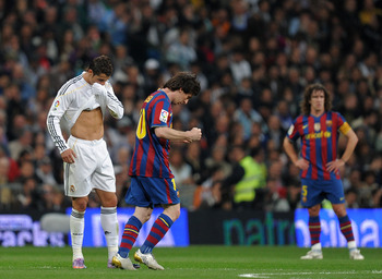 MADRID, SPAIN - APRIL 10:  Lionel Messi (R) of FC Barcelona clenches his fists celebrating scoring his sides opening goal backdropped by Cristiano Ronaldo of Real Madrid during the La Liga match between Real Madrid and Barcelona at the Estadio Santiago Be