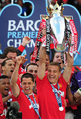 MANCHESTER, ENGLAND - MAY 22:  Captain Nemanja Vidic of Manchester United lifts the Premier League trophy alongside Javier Hernandez after the Barclays Premier League match between Manchester United and Blackpool at Old Trafford on May 22, 2011 in Manches