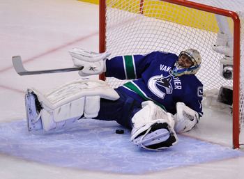 VANCOUVER, CANADA - MAY 24:  Goaltender Roberto Luongo #1 of the Vancouver Canucks falls back into the net after making a save in the first period in Game Five of the Western Conference Finals against the San Jose Sharks during the 2011 Stanley Cup Playof