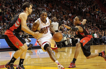 MIAMI, FL - JANUARY 22: Mario Chalmers #15 of the Miami Heat dribbles through DeMar DeRozan #10 and Jose Calderon #8 of the Toronto Raptors during a game at American Airlines Arena on January 22, 2011 in Miami, Florida. NOTE TO USER: User expressly acknow
