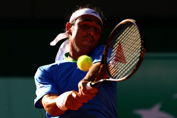 PARIS, FRANCE - MAY 23:  Marcos Baghdatis of Cyprus plays a backhand during the men's singles first round match between Marcos Baghdatis of Cyprus and Frederico Gil of Portugal on day two of the French Open at Roland Garros on May 23, 2011 in Paris, Franc