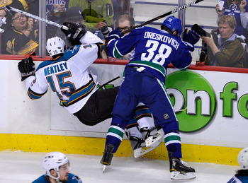 VANCOUVER, CANADA - MAY 24:  Victor Oreskovich #38 of the Vancouver Canucks checks Dany Heatley #15 of the San Jose Sharks in the first period in Game Five of the Western Conference Finals during the 2011 Stanley Cup Playoffs at Rogers Arena on May 24, 20
