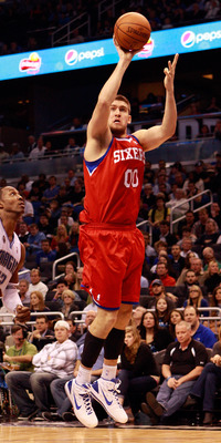 ORLANDO, FL - DECEMBER 18:  Spencer Hawes #00 of the Philadelphia 76ers attempts a shot against Dwight Howard #12 of the Orlando Magic during the game at Amway Arena on December 18, 2010 in Orlando, Florida.  NOTE TO USER: User expressly acknowledges and