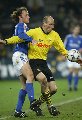 DORTMUND, GERMANY - JANUARY 30:  Niels Oude Kamphuis of Dortmund in action against Jan Koller of Schalke during the Bundsliga match between Borussia Dortmund and  FC Schalke 04 at The Westfallen Stadium on 30 January, 2004 in Dortmund, Germany. (Photo by