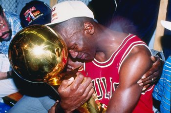 INGLEWOOD, CA - JUNE 12: Guard Michael Jordan #23 of the Chicago Bulls sits nexts to his wife Juanita and his dad James while hugging the NBA Championship Trophy after the Bulls defeated the Los Angeles Lakers 4-1 after Game 5 of the NBA Finals on June 12