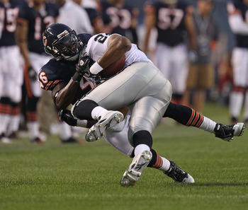 CHICAGO - AUGUST 21: Chris Harris #46 of the Chicago Bears tackles Michael Bush #29 of the Oakland Raiders during a preseason game at Soldier Field on August 21, 2010 in Chicago, Illinois. The Raiders defeated the Bears 32-17. (Photo by Jonathan Daniel/Ge