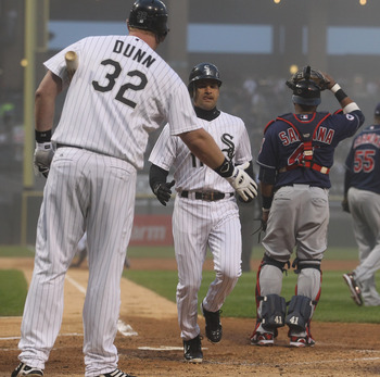 CHICAGO, IL - MAY 19:  Adam Dunn #32 of the Chicago White Sox congratulates teammate Omar Vizquel #11 as he scores a run in the 2nd inning past Carlos Santana #41 of the Cleveland Indians at U.S. Cellular Field on May 19, 2011 in Chicago, Illinois. (Photo