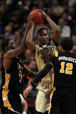 CHICAGO, IL - MARCH 20:  JaJuan Johnson #25 of the Purdue Boilermakers looks to pass against Jamie Skeen #21 and Joey Rodriguez #12 of the Virginia Commonwealth Rams in the second half during the third round of the 2011 NCAA men's basketball tournament at