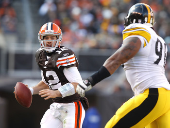 CLEVELAND, OH - JANUARY 02:  Quarterback Colt McCoy #12 of the Cleveland Browns looks for a receiver as he is chased by defensive end Ziggy Hood #96 of the Pittsburgh Steelers at Cleveland Browns Stadium on January 2, 2011 in Cleveland, Ohio.  (Photo by M