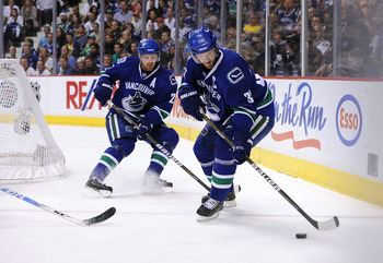 VANCOUVER, CANADA - MAY 24:  Henrik Sedin #33 of the Vancouver Canucks controls the puck as teammate Daniel Sedin #22 looks on in Game Five of the Western Conference Finals against the San Jose Sharks during the 2011 Stanley Cup Playoffs at Rogers Arena o