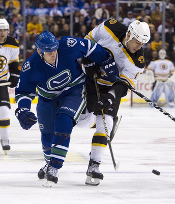 VANCOUVER, CANADA - FEBRUARY 26: Sami Salo #6 of the Vancouver Canucks ties up Milan Lucic #17 of the Boston Bruins during the first period in NHL action on February 26, 2011 at Rogers Arena in Vancouver, British Columbia, Canada.  (Photo by Rich Lam/Gett