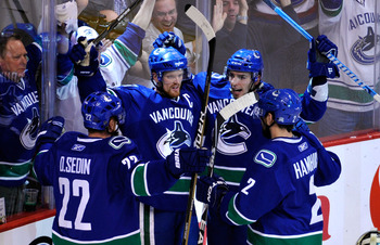 VANCOUVER, CANADA - MAY 24:  (L-R) Daniel Sedin #22, Henrik Sedin #33, Alex Burrows #14 and Dan Hamhuis #2 of the Vancouver Canucks celebrate Burrows' first period goal in Game Five of the Western Conference Finals against the San Jose Sharks during the 2