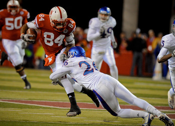LINCOLN, NE - NOVEMBER 13: Brandon Kinnie #84 of the Nebraska Cornhuskers tries to avoid Phillip Strozier #26 of the Kansas Jayhawks during first half action of their game at Memorial Stadium on November 13, 2010 in Lincoln, Nebraska. (Photo by Eric Franc