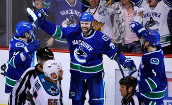 VANCOUVER, CANADA - MAY 18:  Aaron Rome #29 of the Vancouver Canucks celebrates his third period goal with teammates Alex Burrows #14 and Christian Ehrhoff #5 as Ben Eager #55 of the San Jose Sharks skates by in Game Two of the Western Conference Finals d