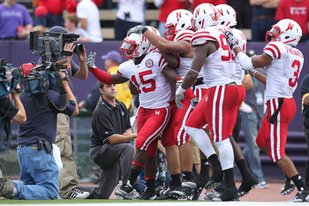 SEATTLE - SEPTEMBER 18:  Cornerback Alfonzo Dennard #15 of the Nebraska Cornhuskers is mobbed by teammates after returning an interception 31 yards for a touchdown in the third quarter against the Washington Huskies on September 18, 2010 at Husky Stadium