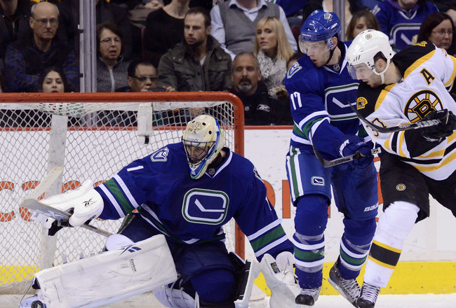 VANCOUVER, CANADA - FEBRUARY 26: Goalie Roberto Luongo #1 of the Vancouver Canucks makes a pad save while Ryan Kesler #17 of the Vancouver Canucks and Patrice Bergeron #37 of the Boston Bruins look on during the second period in NHL action on February 26,