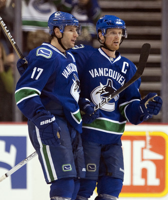 VANCOUVER, CANADA - OCTOBER 17: Ryan Kesler #17 of the Vancouver Canucks celebrates with Henrik Sedin #33 after scoring against the Carolina Hurricanes during the third period in NHL action on October 17, 2010 at Rogers Arena in Vancouver, British Columbi
