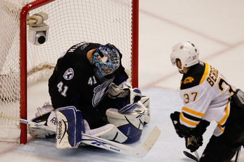 TAMPA, FL - MAY 21:  Mike Smith #41 of the Tampa Bay Lightning makes a save as Patrice Bergeron #37 of the Boston Bruins looks on in Game Four of the Eastern Conference Finals during the 2011 NHL Stanley Cup Playoffs at St Pete Times Forum on May 21, 2011