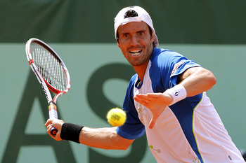PARIS, FRANCE - MAY 28: Juan Ignacio Chela of Argentina hits a forehand during the men's singles round three match between Juan Ignacio Chela of Argentina and Lukas Rosol of Czech Republic on day seven of the French Open at Roland Garros on May 28, 2011 i
