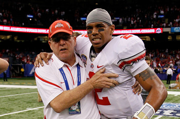 NEW ORLEANS, LA - JANUARY 04:  (M) Quarterback Terrelle Pryor #2 of the Ohio State Buckeyes is helped off the field by a member of the Buckeyes support team after the Buckeyes 31-26 victory against the Arkansas Razorbacks during the Allstate Sugar Bowl at