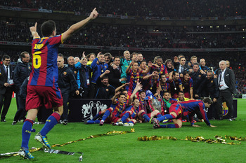 LONDON, ENGLAND - MAY 28:  Xavi (L) runs to join teammates ad Barcelona pose for photographs as they celebrate victory in the UEFA Champions League final between FC Barcelona and Manchester United FC at Wembley Stadium on May 28, 2011 in London, England.