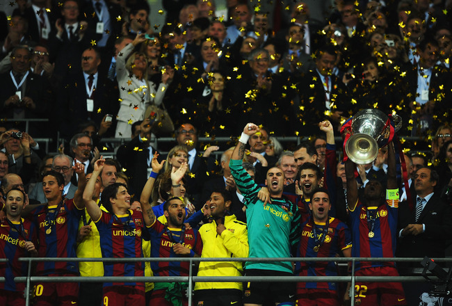 LONDON, ENGLAND - MAY 28:  Eric Abidal (R) of FC Barcelona lifts the trophy and celebrates with teammates after victory in the UEFA Champions League final between FC Barcelona and Manchester United FC at Wembley Stadium on May 28, 2011 in London, England.