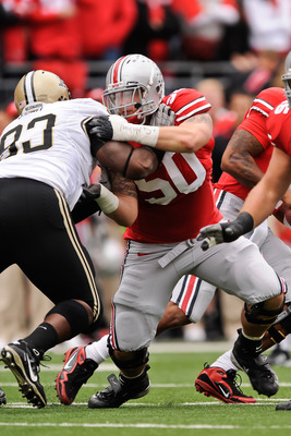 COLUMBUS, OH - OCTOBER 23:  Michael Brewster #50 of the Ohio State Buckeyes blocks against the Purdue Boilermakers at Ohio Stadium on October 23, 2010 in Columbus, Ohio.  (Photo by Jamie Sabau/Getty Images)