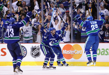 VANCOUVER, BC - MAY 24:  (L-R) Alexander Edler #23, Alex Burrows #14 and Henrik Sedin #33 of the Vancouver Canucks celebrate Kesler's game-tying goal at 2-2 with less than 14 seconds in the third period to send the game into overtime in Game Five of the W