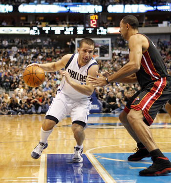 DALLAS - NOVEMBER 27: Jose Barea #11 of the Dallas Mavericks drives by Juwan Howard #5 of the Miami Heat on November 27, 2010 at the American Airlines Center in Dallas, Texas. NOTE TO USER: User expressly acknowledges and agrees that, by downloading and o