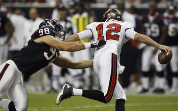 HOUSTON - SEPTEMBER 02:  Quarterback Rudy Carpenter #12 of the Tampa Bay Buccaneers scrambles out of the pocket as he is pressured by defensive end Connor Barwin #98 of the Houston Texans at Reliant Stadium on September 2, 2010 in Houston, Texas.  (Photo