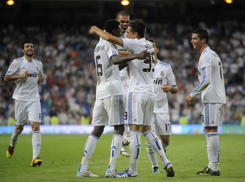 MADRID, SPAIN - MAY 21:  Joselu (R) of Real Madrid celebrates with Emmanuel Adebayor (L) and Cristiano Ronaldo after scoring Real's 8th goal during the La Liga match between Real Madrid and UD Almeria at Estadio Santiago Bernabeu on May 21, 2011 in Madrid