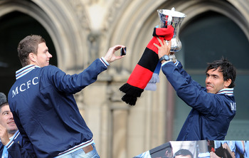 MANCHESTER, ENGLAND - MAY 23:  Carlos Tevez of Manchester City lifts the FA Cup as team-mate Edin Dzeko(L) films him on his mobile phone during the Manchester City FA Cup Winners Parade at Manchester Town Hall on May 23, 2011 in Manchester, United Kingdom