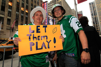 NEW YORK, NY - APRIL 28:  New York Jets fans Peter Merante Sr. and his son Peter Jr. hold up a sign which reads 'Let them play!' on the street outside the venue prior to the 2011 NFL Draft at Radio City Music Hall on April 28, 2011 in New York City.  (Pho