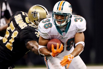 NEW ORLEANS - AUGUST 30:   Patrick Cobbs #38 of the Miami Dolphins avoids a tackle by Brian Simmons #51 of the New Orleans Saints on August 30, 2007 at the Superdome in New Orleans, Louisiana.  (Photo by Chris Graythen/Getty Images)