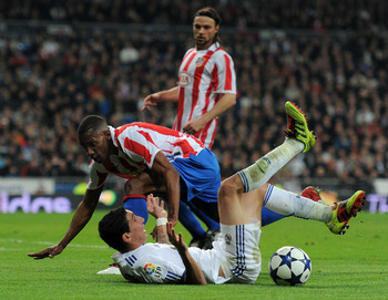 MADRID, SPAIN - JANUARY 13:  Luis Perea (L) of Atletico Madrid fouls Angel Di Maria of Real Madrid during the quarter-final Copa del Rey first leg match between Real Madrid and Atletico Madrid at Estadio Santiago Bernabeu on January 13, 2011 in Madrid, Sp