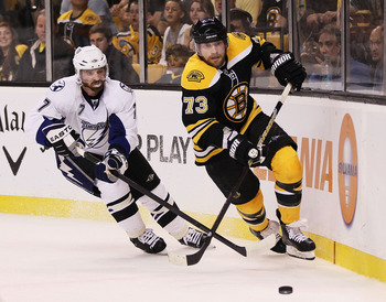 BOSTON, MA - MAY 27: Brett Clark #7 of the Tampa Bay Lightning and Michael Ryder #73 of the Boston Bruins vie for the puck in the first period of Game Seven of the Eastern Conference Finals during the 2011 NHL Stanley Cup Playoffs at TD Garden on May 27,