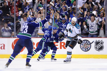 VANCOUVER, CANADA - MAY 24:  (L-R) Alexander Edler #23, Ryan Kesler #17 and Alex Burrows #14 of the Vancouver Canucks celebrate Kesler's game-tying goal at 2-2 with less than 14 seconds in the third period to send the game into overtime as Joe Thornton #1