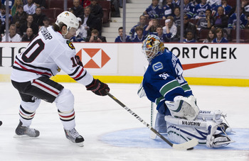 VANCOUVER, CANADA - APRIL 21: Goalie Cory Schneider #35 of the Vancouver Canucks gets his pad down to stop Patrick Sharp #10 of the Chicago Blackhawks during the third period in Game Five of the Western Conference Quarterfinals during the 2011 NHL Stanley