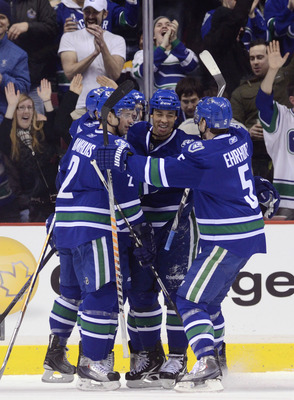 VANCOUVER, CANADA - FEBRUARY 26: Manny Malhotra #27 of the Vancouver Canucks is congratulated by Dan Hamhuis #2 and Christian Ehrhoff #5 after scoring against the Boston Bruins during the first period in NHL action on February 26, 2011 at Rogers Arena in