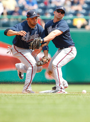 PITTSBURGH - MAY 25:  Alex Gonzalez #2 and Dan Uggla #26 of the Atlanta Braves collide when trying to both make a play at second base during the game against the Pittsburgh Pirates on May 25, 2011 at PNC Park in Pittsburgh, Pennsylvania.  (Photo by Jared