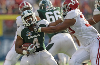 ORLANDO, FL - JANUARY 01:  Edwin Baker #4 of the Michigan State Spartans stiff arms Dont'a Hightower #30 of the Alabama Crimson Tide during the Capitol One Bowl at the Florida Citrus Bowl on January 1, 2011 in Orlando, Florida.  (Photo by Mike Ehrmann/Get