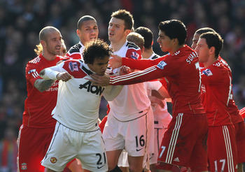LIVERPOOL, ENGLAND - MARCH 06:  Rafael of Manchester United is restrained following his challenge on Lucas of Liverpool during the Barclays Premier League match between Liverpool and Manchester United at Anfield on March 6, 2011 in Liverpool, England.  (P