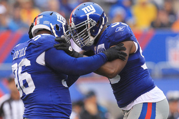 EAST RUTHERFORD, NJ - SEPTEMBER 12: Barry Cofield #96 of the New York Giants celebrates with team mate Chris Canty #99 after sacking Matt Moore #3 of the Carolina Panthers during the NFL season opener at New Meadowlands Stadium on September 12, 2010 in Ea