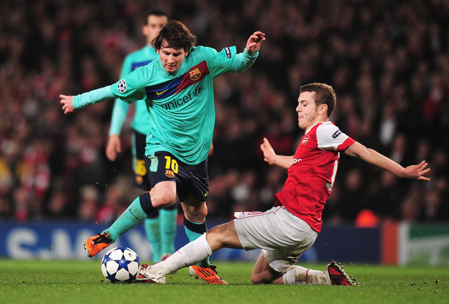 LONDON, ENGLAND - FEBRUARY 16: Lionel Messi of Barcelona is challenged by  Jack Wilshere of Arsenal   during the UEFA Champions League round of 16 first leg match between Arsenal and Barcelona at the Emirates Stadium on February 16, 2011 in London, Englan