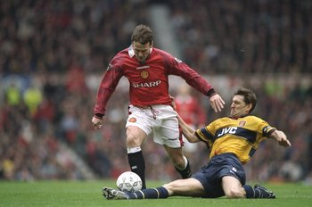 14 Mar 1998:  Tony Adams (right) of Arsenal tackles Teddy Sheringham of Manchester United during an FA Carling Premiership match at Old Trafford in Manchester, England. Arsenal won the match 1-0. \ Mandatory Credit: Shaun  Botterill/Allsport
