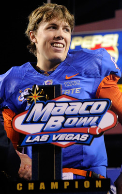 LAS VEGAS, NV - DECEMBER 22:  Quarterback Kellen Moore #11 of the Boise State Broncos smiles while standing behind a trophy as he celebrates the team's 26-3 victory over the Utah Utes in the MAACO Bowl Las Vegas at Sam Boyd Stadium December 22, 2010 in La