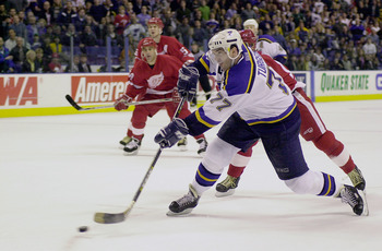 10 Mar 2001: Pierre Turgeon #77 of the St. Louis Blues takes a shot against Chris Osgood #30 of the Detroit Red but hits the post during the overtime period at the Savvis Center in St. Louis, Missouri. The St.Louis Blues and the Detroit Red Wings tied at