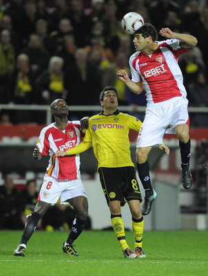 SEVILLE, SPAIN - DECEMBER 15: Nuri Sahin of Borussia Dortmund (C), Didier Zokora of Sevilla FC (L) and Federico Fazio of Sevilla FC duel for a high ball during the UEFA Europa League group J match between Sevilla and Borussia Dortmund at Estadio Ramon San