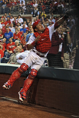 PHILADELPHIA, PA - MAY 23: Carlos Ruiz #51 of the Philadelphia Phillies jumps into the backstop to catch a foul ball during the game against the Cincinnati Reds at Citizens Bank Park on May 23, 2011 in Philadelphia, Pennsylvania. The Phillies won 10-3. (P