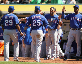 OAKLAND, CA - APRIL 30:  Adrian Beltre #29 and Mike Napoli #25 of the Texas Rangers are congratulated by teammates after they scored on a double by Yorvit Torrealba #8 of the Texas Rangers in the eighth inning of their game against the Oakland Athletics a
